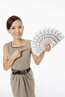 Businesswoman pointing at a pile of cash