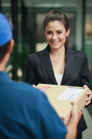 Businesswoman receiving package from delivery person