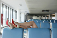 Businesswoman resting her legs on seat in airport lounge