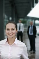 Businesswoman smiling, businessmen in the background