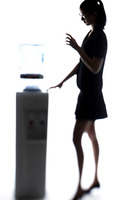 Businesswoman taking water from the water dispenser