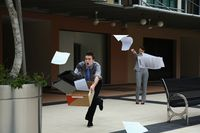 Businesswoman throwing papers, businessman catching them