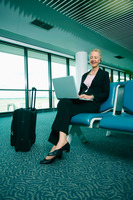 Businesswoman using laptop at airport lounge