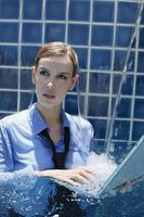 Businesswoman using laptop in swimming pool