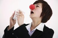Businesswoman wearing a clown's nose about to sneeze into tissue
