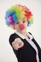 Businesswoman wearing a clown's wig and nose pointing with finger