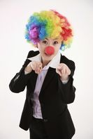 Businesswoman wearing a clown's wig and nose pointing with index fingers