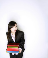 Businesswoman with a stack of books looking up in shock