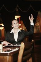 Businesswoman with arms raised gesturing to waiter