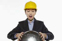 Businesswoman with construction helmet holding a globe