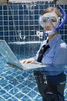 Businesswoman with diving mask using laptop in swimming pool