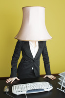 Businesswoman with lampshade on head