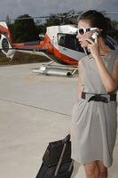 Businesswoman with luggage and briefcase talking on the phone at helipad