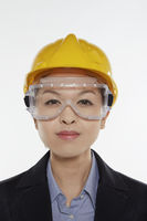 Businesswoman with safety glasses and construction helmet smiling at the camera