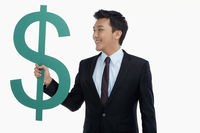 Cheerful businessman holding up a dollar sign