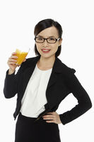 Cheerful businesswoman holding a glass of orange juice