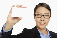 Cheerful businesswoman holding up a blank business card