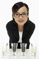 Cheerful businesswoman with an assortment of shot glasses