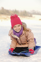 Cheerful girl riding on sled