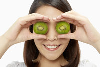 Cheerful woman covering her eyes with a kiwi