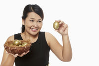 Cheerful woman holding up a golden egg