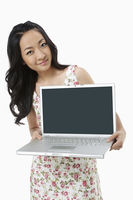 Cheerful woman holding up a laptop