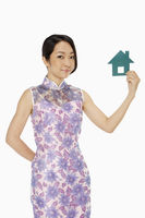 Cheerful woman holding up a paper house