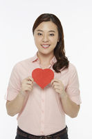 Cheerful woman holding up a red heart