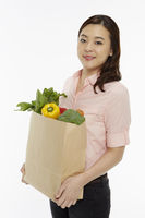 Cheerful woman with a bag of groceries