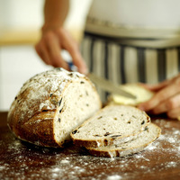 Chef slicing country olive bread