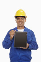 Construction worker holding up a digital tablet