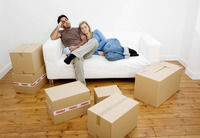 Couple napping on the couch with boxes on the floor
