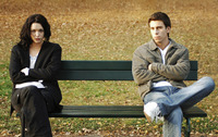 Couple sitting on different ends of a bench