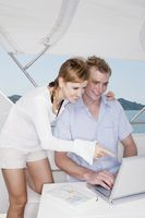 Couple using laptop on yacht with books on the table