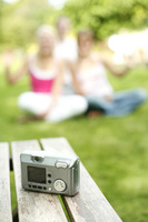 Digital camera on table with teenage girls posing in the background