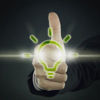 Digital graphic of a light bulb against thumbs up gesture
