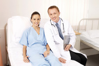 Doctor and patient sitting on bed smiling
