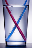 Drinking straw crossing in a glass of water