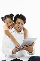 Father and daughter using a digital tablet together