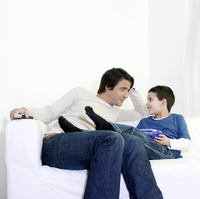 Father and son sitting on the couch chatting