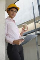 Female architect holding a cup of coffee and clipboard