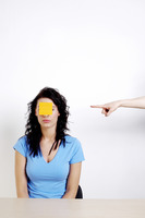 Finger pointing at a woman with a paper pasted on her face