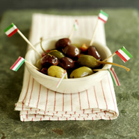 Fresh italian olives in a small ceramic bowl with italian flag picks sitting on a red stripy napkin