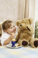 Girl having breakfast with teddy bear