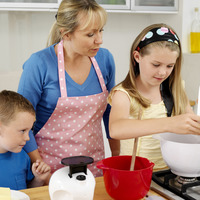 Girl pouring flour into mixing bowl, woman and boy watching