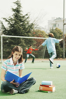 Girl reading while her friends are playing soccer