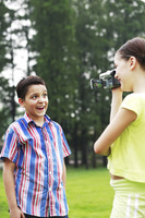 Girl recording images of boy making a face