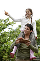 Girl sitting on man's shoulders with man holding a basket of pears