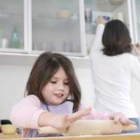 Girl using rolling pin with her mother in the background