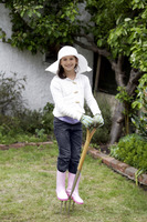 Girl with straw hat, gardening gloves and boots standing on a pitchfork
